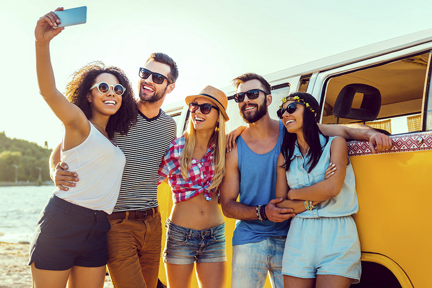 Group of happy young people bonding to each other and making selfie while standing near their retro mini van