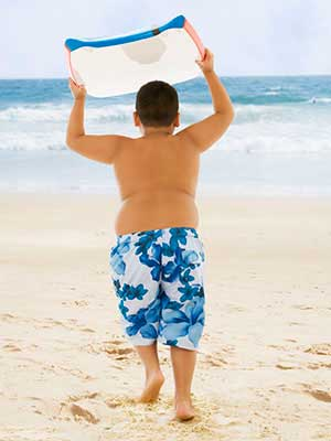 Boy carrying boogie board to ocean