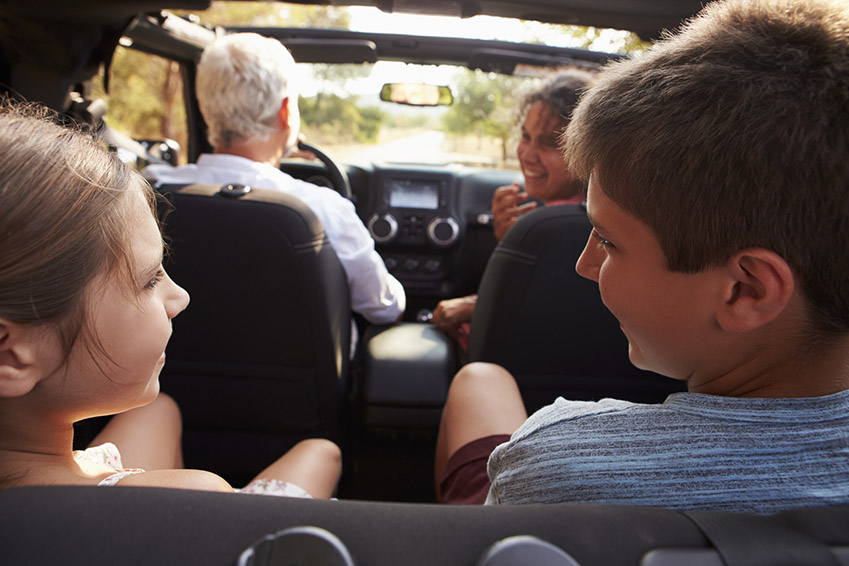 Grandparents Taking Grandchildren On Trip In Open Top Car